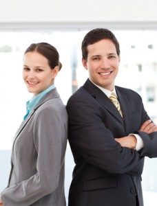 Happy businessman and businesswoman posing back to back